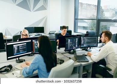 Personas que trabajan en la oficina moderna. Grupo de jóvenes programadores sentados en escritorios trabajando en computadoras en su oficina. Equipo en el trabajo. Imagen de alta calidad