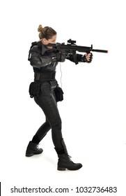 Porträt in voller Länge des weiblichen Soldaten, der schwarze taktische Rüstung hält, die eine Waffe hält, lokalisiert auf weißem Studiohintergrund.
