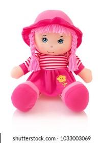 Muñeca de peluche rosa aislado sobre fondo blanco con sombra de reflexión. Muñeca linda del trapo del meñique que se sienta en la capa inferior blanca. Bonito bebé de trapo contemporáneo con cabello rosado. Moderno bebé alegremente trapo con gorra.