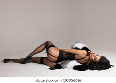 黒のランジェリー、ストッキング、毛皮を身に着けている白い背景の上に横たわるスタジオでエレガントなブルネットの女性のファッションの肖像画。