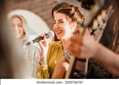 Entertianment at a wedding. A female singer is interacting with the crowd while a man plays an acoustic guitar.