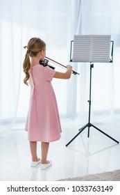 Rückansicht des kleinen Kindes im rosa Kleid, das zu Hause Geige spielt