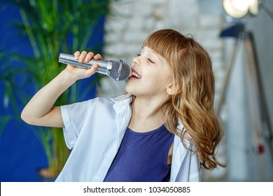 Little beautiful child singing into the microphone. The concept is childhood, lifestyle, music, singing, listening, hobbies.
