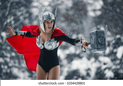 Young woman in image of Germanic-Scandinavian God of thunder and storm are waving hammer in fury against winter forest background. Cosplay.