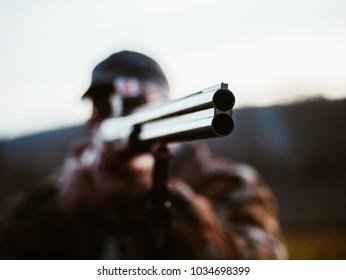 Ciérrese para arriba del arma de caza del barril doble. El hombre cazador con abrigo cálido apunta al enemigo en el campo de batalla con un rifle. Un hombre irreconocible caza en el bosque. Centrarse en barril