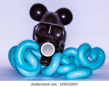 Matte black gas mask with black balloons sticking like mickey mouse ears sits on curled sausage ballons of baby-blue color on white background isolated