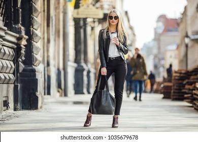 Junges hübsches Mädchen gehen auf der Straße mit Tasse Kaffee auf der Hand und tragen Sonnenbrille, sonniges Tageswetter