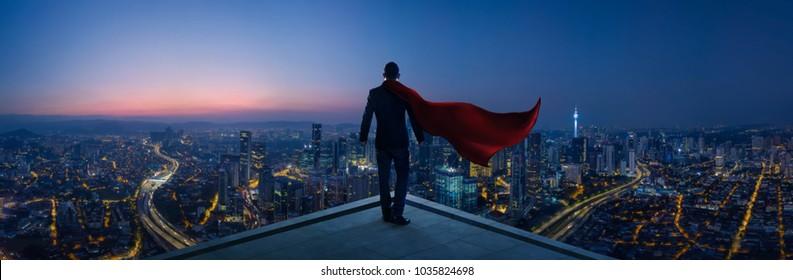 Hombre de negocios en traje y héroe del cabo de pie en la azotea con una gran vista del paisaje urbano y pensando en el plan de negocios del futuro. Escena nocturna .