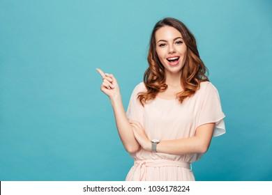 青い背景の上に孤立して立っている幸せな若い女性の画像。カメラポインティングを探しています。