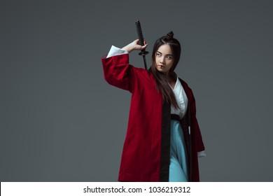 Samurai im Kimono hält Katana-Schwert und schaut isoliert auf Grau weg