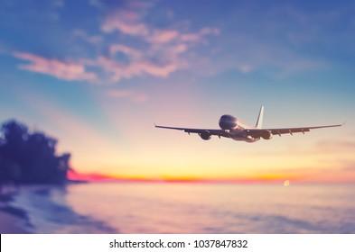 上空を飛ぶ飛行機は、熱帯のビーチと夕焼け空の抽象的な背景をぼかします。ビジネスの夏休みと旅行の冒険のコンセプトのコピースペース。ヴィンテージトーンフィルターカラー。