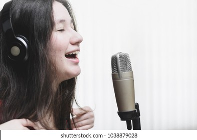 Woman singing at a studio microphone, wearing a headphone. Woman smiling while she sings. White background.