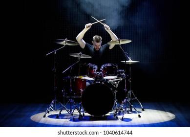 Schlagzeuger spielt Schlagzeug mit Rauch und Puder im Hintergrund