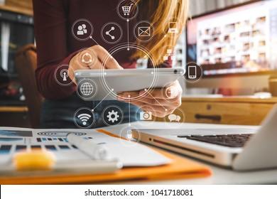 朝の光の中でmodernofficeで仮想アイコン図と現代のオフィスでラップトップコンピューター、タブレット、スマートフォンで作業する実業家の手