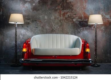 Ein handgemachtes Sofa und eine Lampe auf einem Grunge-Artwandhintergrund. Auf Bestellung vom Autositz aus angefertigt.