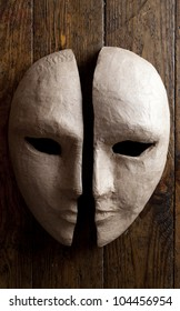 Two halves of the paper masks on a wooden background