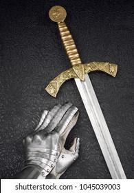 Ein schönes altes Schwert des Ordens der Tempelritter und ein eiserner Ritterhandschuh auf einem dunklen schönen Hintergrund.