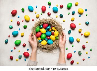 春のイースターの背景。女性の手はイースターのカラフルな卵の巣を保持しています。イースターフラット横たわっていた装飾。春の休日。トップビューの抽象的な創造的な構成。春の気分。
