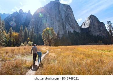 2人のアクティブな家族、父と息子の背面図、ヨセミテ国立公園、カリフォルニア、アクティブな家族の休暇の概念で谷と山の景色を楽しんでいます