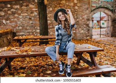 Mujer joven despreocupada en pantalones de moda vintage sentado en la mesa en el parque y riendo. Linda chica rizada de buen humor posando en día de otoño, disfrutando del buen tiempo.