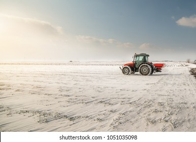Agricultor con tractor sembrando - sembrando cultivos en campos agrícolas en invierno - nieve