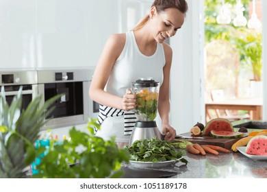 スイカとニンジンでスムージーを作るビーガン女性の笑顔