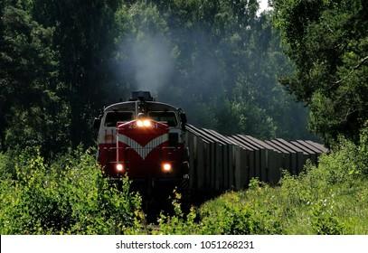 貨物列車または貨物列車が近づいています、蒸気は赤い機関車から来ています