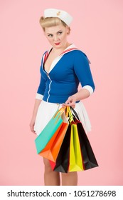 Young happy woman in animation style with colored shopping bags on rose background. Shopping time with anime styled girl in studio isolated. Pin-up styled woman with bags in hand. Sea woman with bags