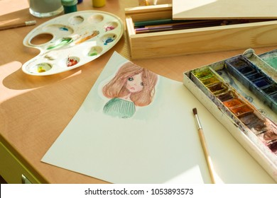 Drawing by watercolor - anime girl, on a table with watercolor paint brush