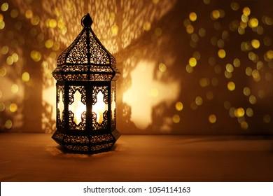 Arabische Zierlaterne mit brennender Kerze, die nachts leuchtet und goldene Bokeh-Lichter glitzert. Festliche Grußkarte, Einladung zum muslimischen heiligen Monat Ramadan Kareem. Dunkler Hintergrund.