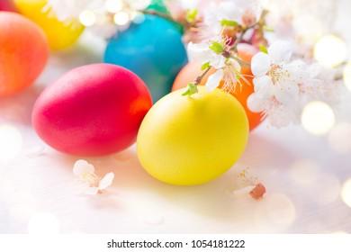 Ostern. Bunte Ostereier mit Frühlingsblütenblumen lokalisiert über weißem Hintergrund. Farbiges Ei-Feiertagsgrenzen-Kunstdesign
