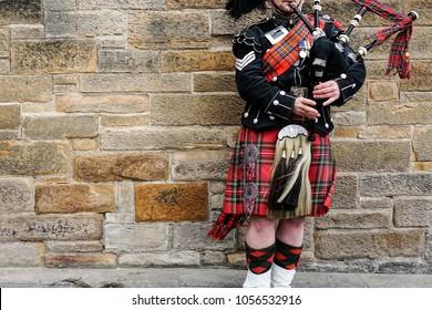 EDINBURGH, SCHOTTLAND, 24. März 2018, schottischer Dudelsackspieler, gekleidet in traditionelles rotes und schwarzes Tartankleid, stehen vor Steinmauer. Edinburgh, das beliebteste Touristenziel in Schottland.