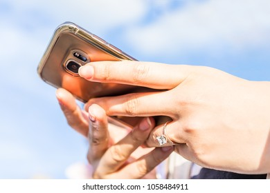 Young woman's hand with diamond engagement ring princess cut, gold outside outdoors blue cloudy sky, closeup of smartphone phone holding