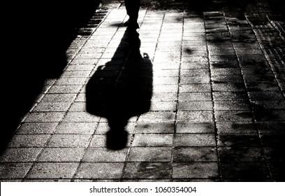 黒と白の水の反射と濡れた街の通りの歩道に夜に立っている男のぼやけた影とシルエット