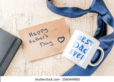 Father's Day gift concept, greeting card background, gift box, tie decoration, mug with inscription Best Dad Ever, notebook, top view