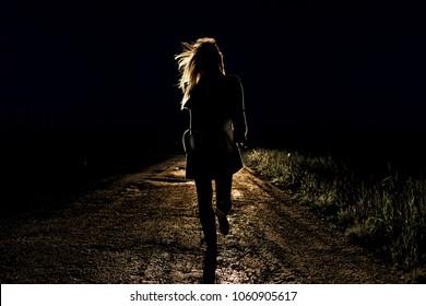 einsame junge verängstigte Frau auf einer leeren Nachtstraße rennt im Licht der Scheinwerfer ihres Autos davon