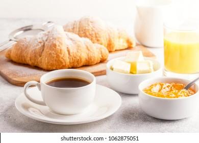Continentaal ontbijt met verse croissants, sinaasappelsap en koffie, selectieve aandacht.