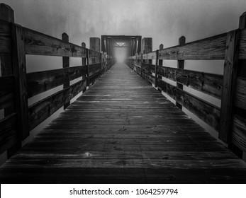 テネシー州ウィンチェスターのティムスフォード州立公園で霧のかかった朝に湖に架かる古いトラス歩道橋の忘れられない白黒画像。SF映画のポータルに似ています。