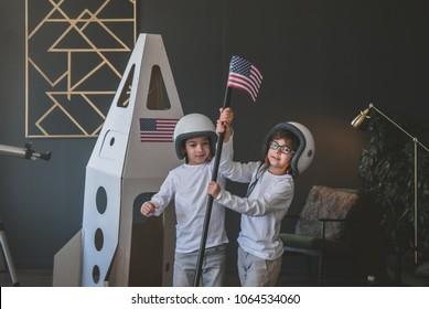 Niedliche kleine Träumergeschwister, die Raumhelme tragen, die vorgeben, Astronauten auf Mond zu sein, US-Flagge nahe Pappraumrakete zu Hause platzierend