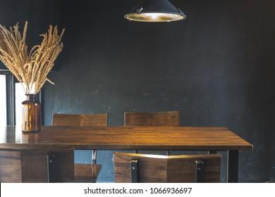 Mesa de comedor oscura con silla de madera y flores secas en sala de diseño vintage