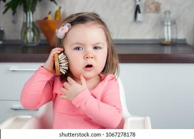 Mädchen 2 Jahre alt spielt mit einem Kamm zu Hause - porträtiert ein emotionales Gespräch am Telefon