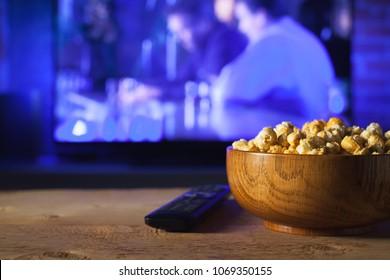 ポップコーンの木製ボウルとテレビが機能するバックグラウンドのリモコン。家で映画やテレビシリーズを見て居心地の良い夜