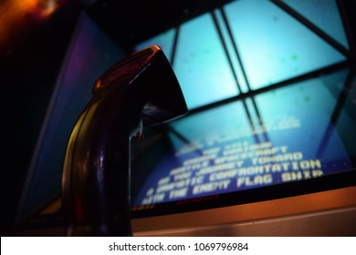 Vintage Arcade Video Game Joystick Close-Up with Game Screen and Blue Lit Cabinet in Background