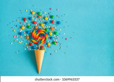 Cono de galleta de helado con paleta de colores en palo, dispersión de dulces multicolores y cobertura de confitería. Fondo azul