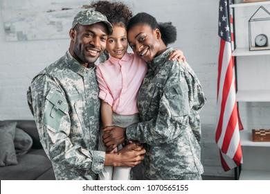 娘を抱きしめるアフリカ系アメリカ人の女性と男性の兵士