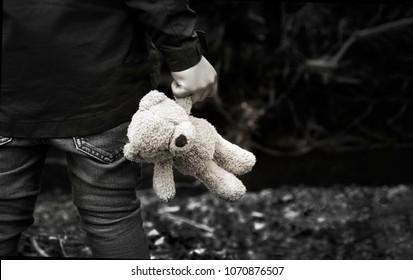 Schwarzweiss-Foto des Kindes, das Teddy hält, der allein im Wald erwacht, Rückansicht eines Jungen, der allein steht und sein Ted, verwöhntes Kind, verlorene Kinder oder obdachloses Kinderkonzept hält