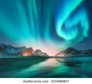 Aurora borealis en las islas Lofoten, Noruega. Aurora. Aurora boreal verde. Cielo estrellado con luces polares. Paisaje invernal nocturno con aurora, mar con reflejo del cielo, piedras, playa y montañas nevadas