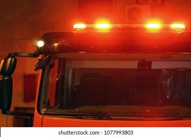 Rote Ampeln eines Feuerwehrautos. Nachtzeit. Feuerwehrauto. Das Feuer löschen. Nahaufnahme der roten Lichter oben auf einem Feuerwehrauto.