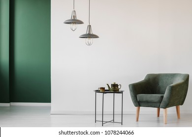 Upholstered, dark armchair and an industrial side table with a tea kettle and cup in a minimalist living room interior with a green corner