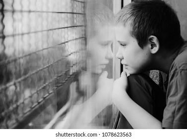 Netter 10 Jahre alter autistischer Junge, der den Regen betrachtet